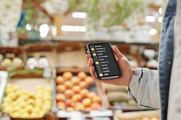 Nahaufnahme eines nicht erkennbaren mannes, der beim kauf von lebensmitteln auf dem bauernmarkt eine checklisten-app verwendet