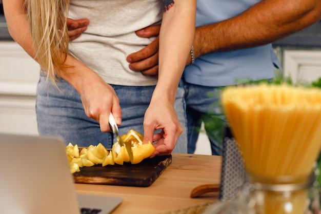 Nahaufnahme eines nicht erkennbaren paares, das in der küche zusammen essen kocht