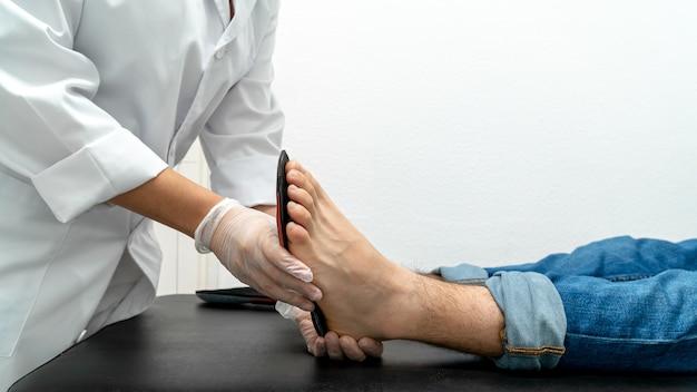 Nahaufnahme eines nicht erkennbaren podologen, der einlegesohlen an einem patienten ausprobiert