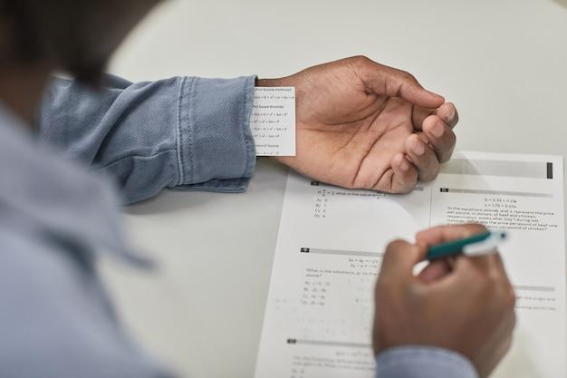 Nahaufnahme eines nicht erkennbaren schülers, der eine cheat-notiz versteckt, während er in der schule eine prüfung ablegt, platz kopieren
