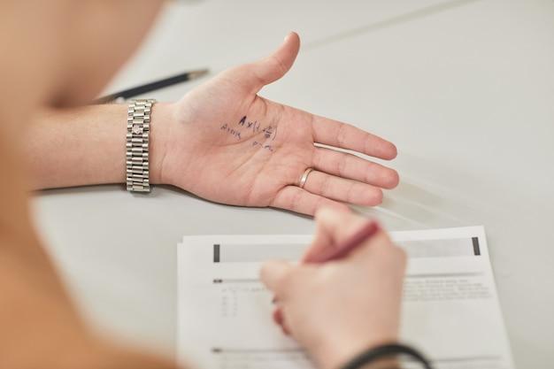 Nahaufnahme eines nicht erkennbaren schülers, der während der prüfung in der schule cheat-notiz liest, platz kopieren