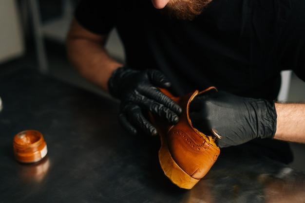 Nahaufnahme eines nicht erkennbaren schusters in schwarzen handschuhen, der farbe auf hellbraunen lederschuhen mit ...