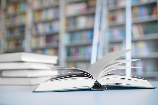 Nahaufnahme eines offenen lehrbuchs, das neben einem stapel geschlossener bücher auf dem tisch liegt