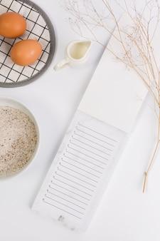 Nahaufnahme eines offenen notizblocks mit rohem ei; mehl und milch