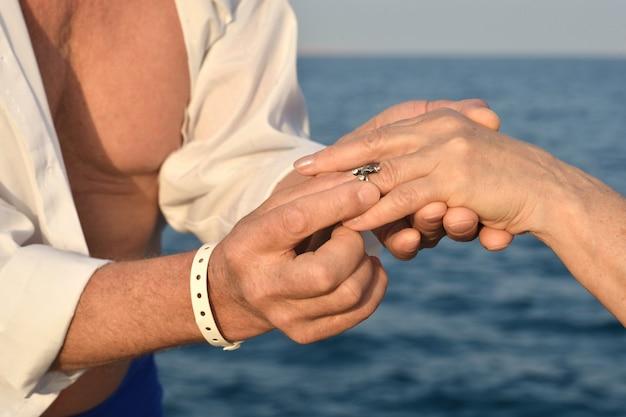 Nahaufnahme eines paares, das eheringe während einer hochzeitszeremonie am strand austauscht.