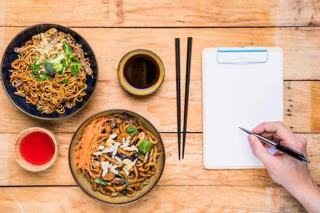Nahaufnahme eines personenschreibens auf klemmbrett mit stift nahe dem thailändischen traditionellen lebensmittel und den soßen auf tabelle