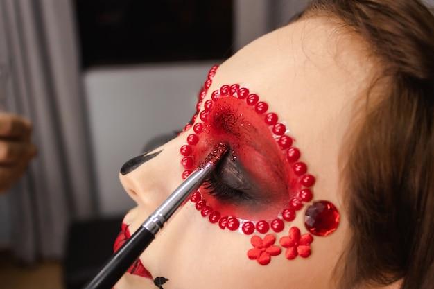 Nahaufnahme eines pinsels, der glitzer am rand der augen eines jungen mädchens hinzufügt, dia de los muertos make-up.
