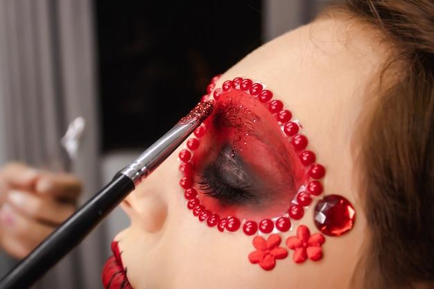 Nahaufnahme eines pinsels, der glitzer am rand der augen eines mädchens hinzufügt, dia de los muertos make-up.