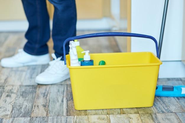 Nahaufnahme eines plastikeimers mit reinigungsmitteln mann, der sich auf die reinigung der hausarbeit vorbereitet