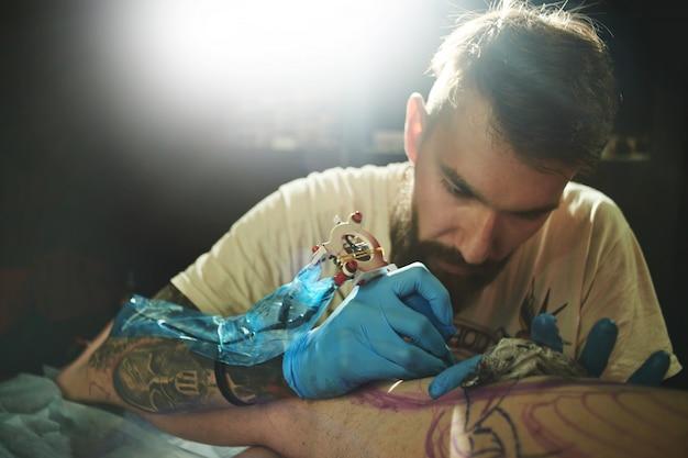 Nahaufnahme eines professionellen bärtigen tätowierers, der einen kunden zu einem mann in einem salon tätowiert