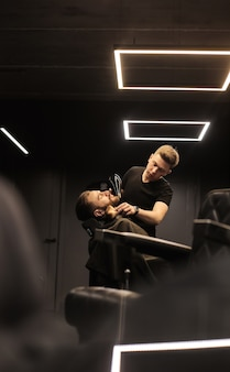 Nahaufnahme eines professionellen friseurs, der den bart seines jungen kunden pflegt, der während des eingriffs in den spiegel schaut.