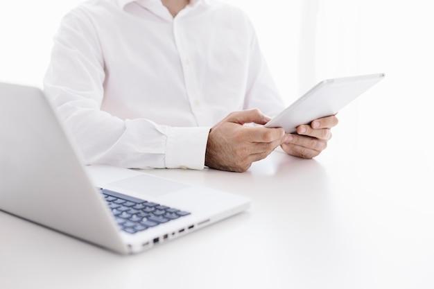 Nahaufnahme eines professionellen geschäftsmannes mit tablet gegen weißen schreibtisch