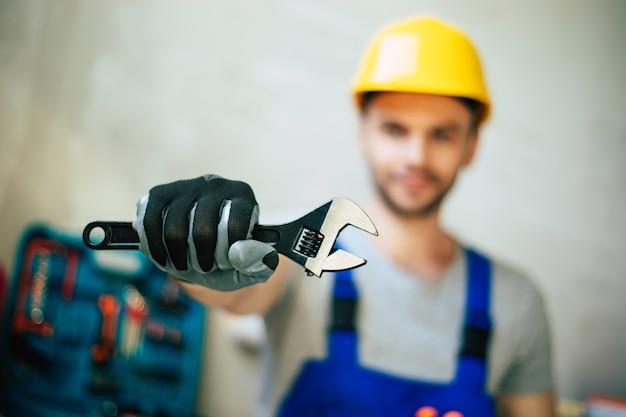 Nahaufnahme eines professionellen mechanikers in uniform und schutzhelm hält in den händen moderne neue werkzeuge für arbeit und renovierung