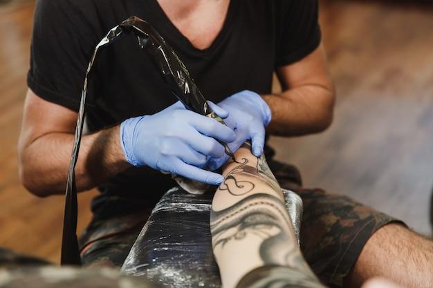 Nahaufnahme eines professionellen tätowierers, der maschinell mit schwarzer tinte am arm eines jungen mannes tätowiert?