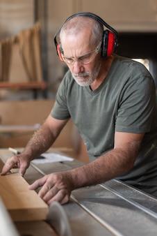 Nahaufnahme eines reifen arbeiters, der in einer fabrik ein holz mit einer maschine schneidet?