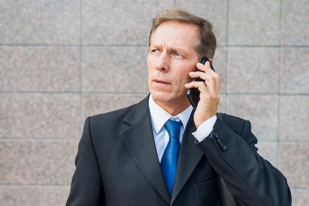 Nahaufnahme eines reifen geschäftsmannes, der auf smartphone spricht