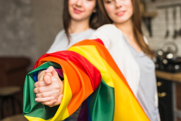Nahaufnahme eines reizenden lesbischen jungen paares, das hände mit eingewickelter lgbt-stolzflagge sich hält
