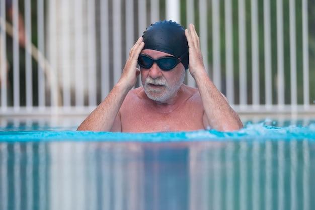 Nahaufnahme eines rentners im pool, der allein beim schwimmen trainiert - aktive menschen und gesunde und fitte senioren - lebensstil des aktiven reifen mannes