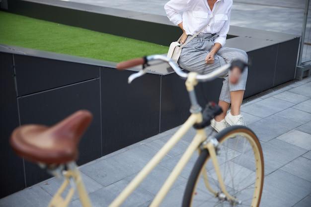 Nahaufnahme eines retro-stadtfahrrads, das vor einer stilvollen frau steht, während sie sich ausruht, nachdem sie zur arbeit gefahren ist