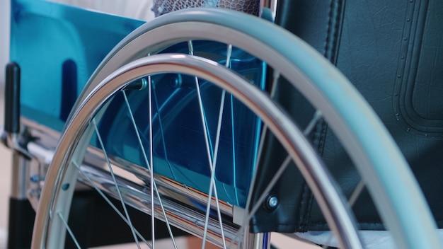 Nahaufnahme eines rollenden rollstuhls mit behinderten patienten im krankenhausflur. behandlung von krankheiten mit behinderungen, behinderungen, behinderungen, und patientenlähmung