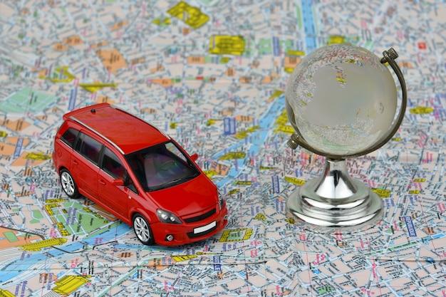 Nahaufnahme eines roten autos und der glaskugel auf einem touristischen kartenhintergrund