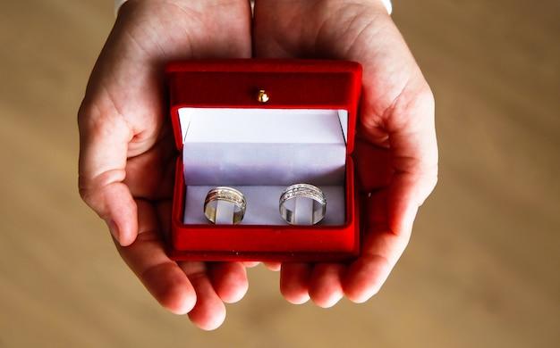 Nahaufnahme eines roten feldes mit zwei ringen für eine verlobung