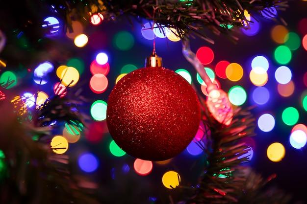 Nahaufnahme eines roten glänzenden weihnachtsballs, der an einem weihnachtsbaum hängt