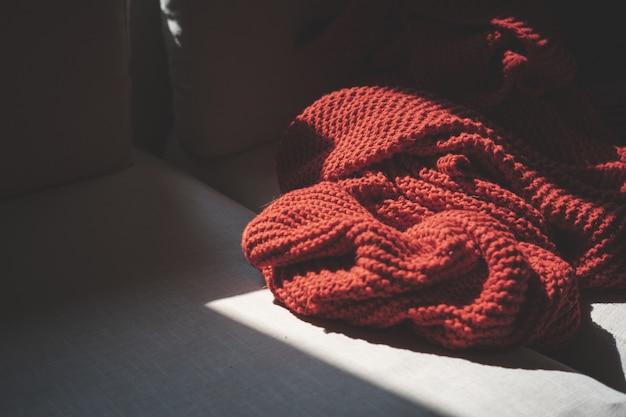 Nahaufnahme eines roten textils auf einer holzoberfläche, die mit dem sonnenlicht beleuchtet wird