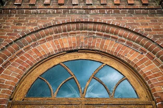 Nahaufnahme eines runden fensters im alten haus eine villa gemacht vom alten ziegelstein