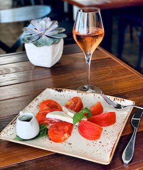 Nahaufnahme eines salats mit käse und tomaten auf einem quadratischen teller mit alkoholischem getränk nahe einer pflanze