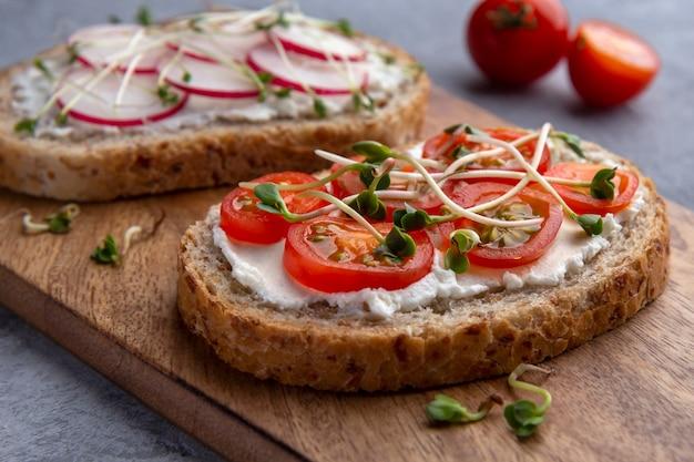 Nahaufnahme eines sandwichs mit gemüse, mikrogrün und getreidebrot auf einer grauen oberfläche