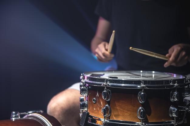 Nahaufnahme eines schlagzeugers, der eine snare-drum mit stöcken auf dunklem hintergrund spielt.