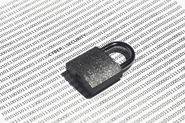 Nahaufnahme eines schlosses auf einer weißen oberfläche mit binärcode darauf - konzept der cybersicherheit