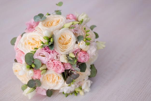 Nahaufnahme eines schönen blumenstraußes auf einem grauen hintergrund. weiche rosa rosen und creme, gelb.