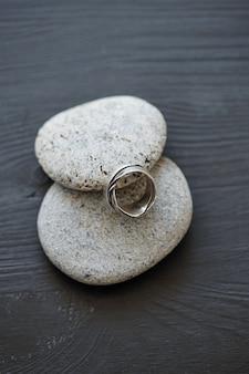 Nahaufnahme eines schönen designer-rings, der sich auf ein kieselstein-foto für website-inhalte stützt