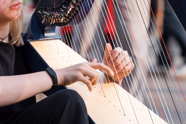 Nahaufnahme eines schönen mädchens, das die harfe spielt. detail einer frau, die die harfe draußen spielt
