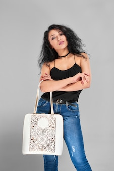 Nahaufnahme eines schönen sexy mädchens mit einem schwarzen lockigen haar, das in ihren blauen jeans, im schwarzen oberteil, im ledergürtel und im unterlegkeil an ihrem hals sehr modisch aussieht. sie trägt eine weiße tasche