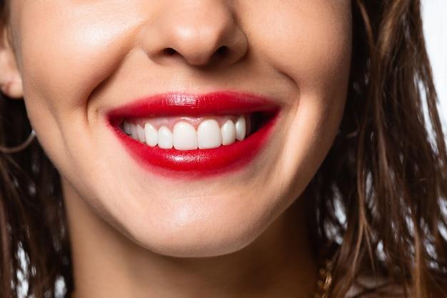 Nahaufnahme eines schönen weiblichen lächelns mit weißen zähnen isoliert auf weißem studiohintergrund