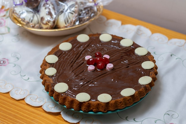 Nahaufnahme eines schokoladenkuchens und des korbs mit ostereiern, die in defokussiertes transparentes papier eingewickelt werden