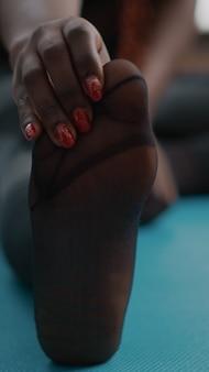 Nahaufnahme eines schwarzen athleten, der mit gespreiztem bein auf dem boden auf der matte sitzt