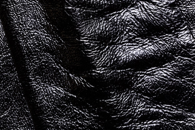 Nahaufnahme eines schwarzen lederbeschaffenheitshintergrundes.