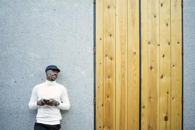 Nahaufnahme eines schwarzen mannes, der einen hut und einen rollkragenpullover trägt, der sein telefon hält