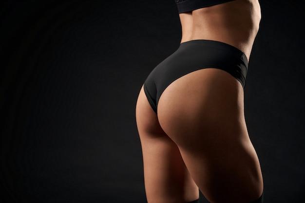 Nahaufnahme eines sexy inkognito-frauenmodells, das schwarze sportunterwäsche trägt, isoliert auf schwarzem studiohintergrund. rückansicht der kaukasischen frau des sitzes mit der perfekten gesäßaufstellung.