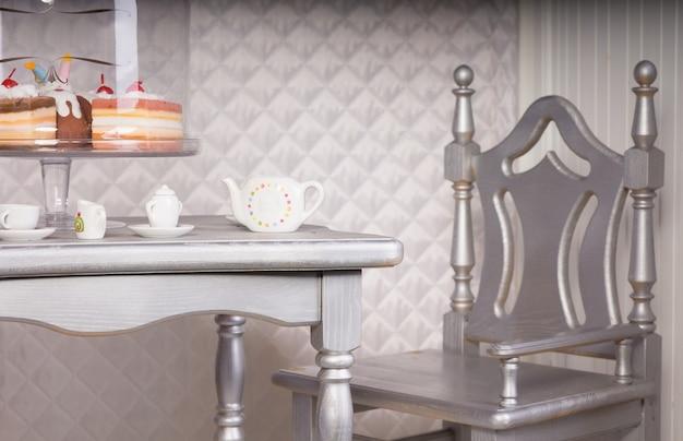 Nahaufnahme eines silbernen stuhls am esstisch für tee mit dekadentem kuchen auf ständer