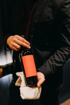 Nahaufnahme eines sommeliers, der eine leere flasche rotwein hält.