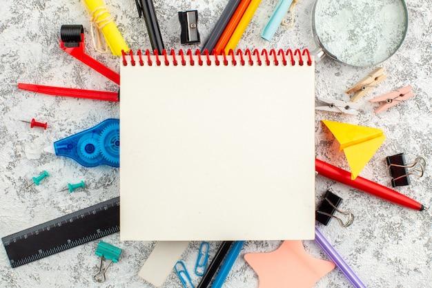 Nahaufnahme eines spiralförmigen geschlossenen spiralnotizbuchs und verschiedener bürogeräte auf weißer oberfläche