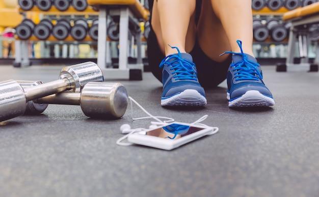 Nahaufnahme eines sportlichen mannes, der auf dem boden des fitnesscenters mit hanteln und smartphone mit kopfhörern im vordergrund sitzt