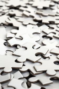 Nahaufnahme eines stapels der unvollständigen elemente eines weißen puzzlespiels