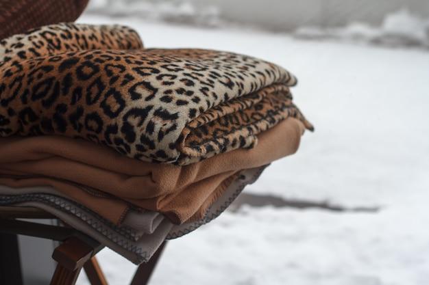 Nahaufnahme eines stapels mehrfarbiger decken, die draußen auf einem stuhl über einer schneebedeckten landschaft liegen