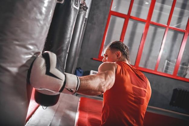 Nahaufnahme eines starken schlags auf den boxsack. selbstbewusster muskulöser sportler in weißen handschuhen, der hart an einem schweren boxsack in der schwarzen boxhalle trainiert